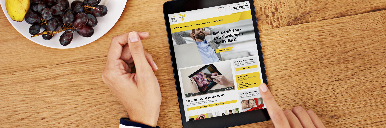 Frau schaut sich die Website der EY BKK auf einem Tablet an